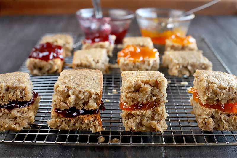 Gluten-free oat sandwich bars filled with orange and red fruit jam on a metal cooling rack, with two small glass bowls of jam with spoons stuck into them in shallow focus in the background, on a dark brown wood table with a brown background.