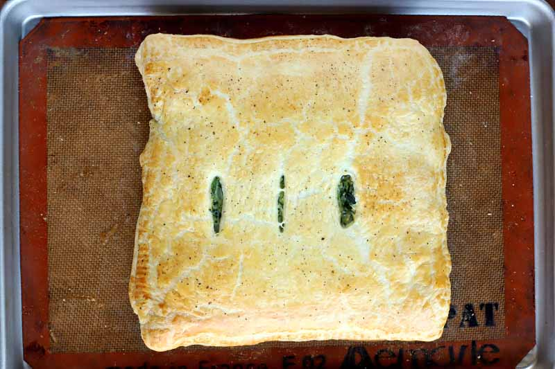 Overhead shot of just-baked spinach in golden brown puff pastry with three vertical vents cut into the top to show the filling, on a well-used tan Silpat silicone pan liner with an orange border, set into a rimmed metal baking sheet.