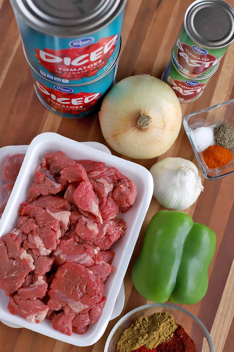 Overhead vertical shot of two cans of diced tomatoes, two cans of tomato paste, a yellow onion, a head of garlic, a square glass dish of various spices, a green bell pepper, and two Styrofoam trays of beef stew meat.