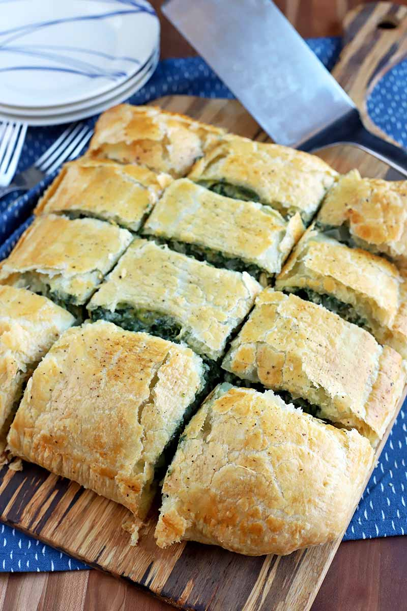 Twelve pieces of homemade spinach filling in golden brown puff pastry on a wood peel with a metal spatula and three blue and white plates alongside a few forks, on a blue place mat with white flecks, on a wood surface.