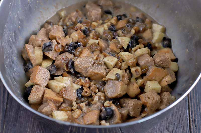 A mixture of egg, spices, fruit, nuts, and cubes of bread in a stainless steel mixing bowl, on a dark brown wood table.