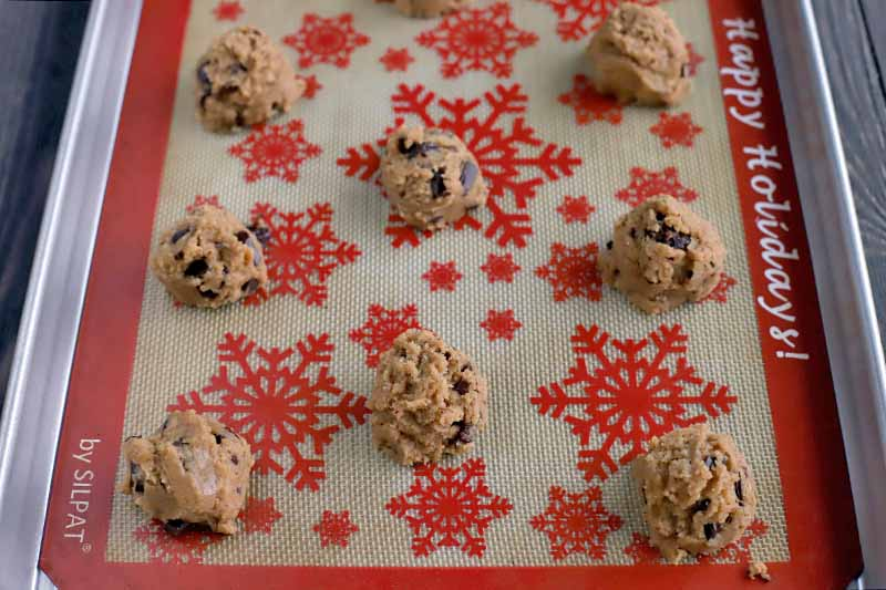 Oblique shot of eight balls of cookie dough arranged in rows on a holiday-themed Silpat silicone pan liner printed with a red border and red snowflakes on a white background, set into a rimmed metal baking sheet.