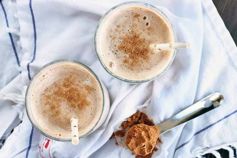 Overhead shot of two glasses of homemade chocolate and banana smoothie with white paper straws, on a white cloth with a scoop of cocoa powder, on a dark brown wood surface.