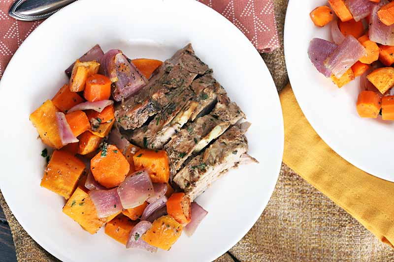Overhead shot of two plates of pork and roasted root vegetables, on a surface topped with burlap and pink and yellow cloth.