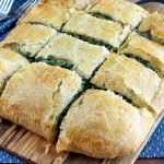 Twelve slices of spinach in puff pastry arranged in rows on a wood serving board and shot at an oblique angle, with forks on top of a blue cloth with white flecks, on a wood background.