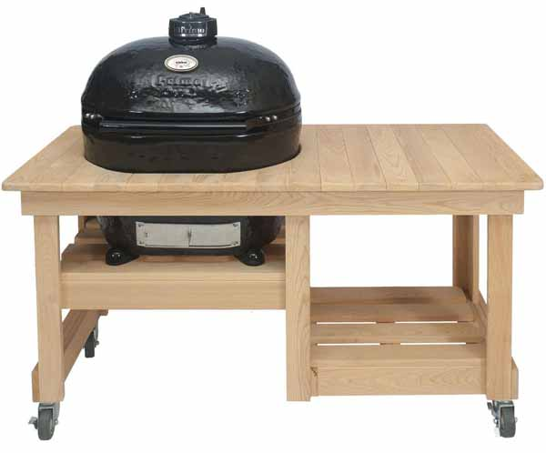 Primo Oval XL Ceramic Kamado Grill On Countertop Cypress Table on a white, isolated background.