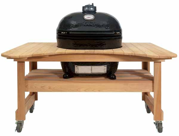 Primo Oval XL Ceramic Kamado Grill On Curved Cypress Table on a white, isolated background.