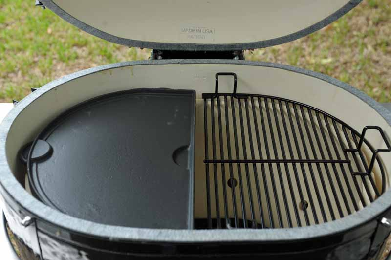One side of the Primo XL 400 Kamado fitted with a half-moon-shaped griddle accessory, with the smooth side showing.