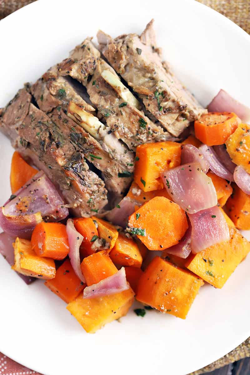 Slices of pork loin with orange vegetables and onion, on a white plate.