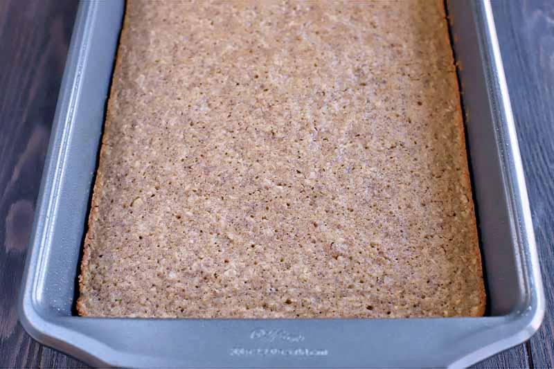 A baked oat mixture in a rectangular metal baking pan, on a dark brown wood surface.