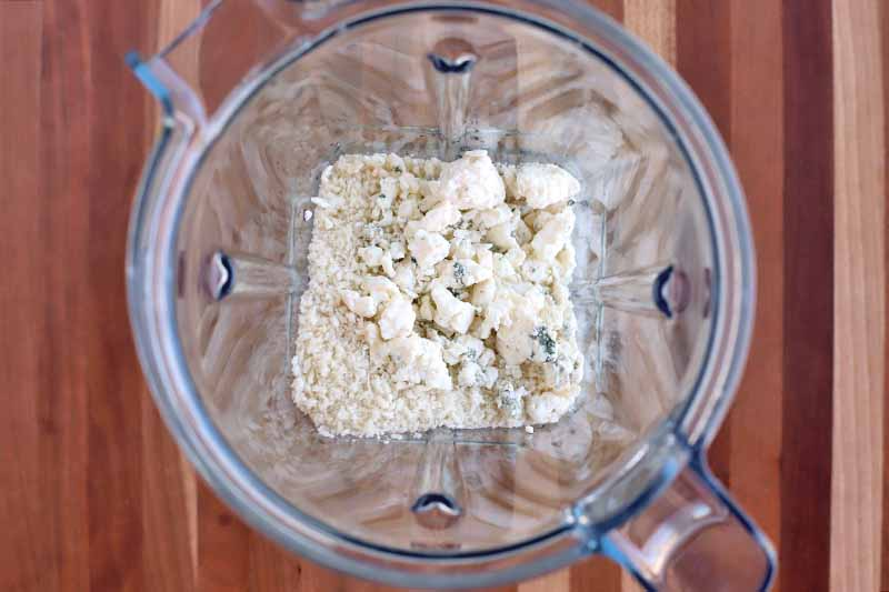 A blue cheese and breadcrumb mixture is at the bottom of a clear pitcher-style blender canister, on a striped brown wood surface.
