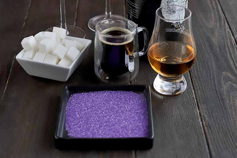 Oblique closely cropped overhead shot of a small square white ceramic dish of white cubes and a shallow square black dish of purple sanding sugar, a small glass mug of espresso, two champagne flutes, a bottle of champagne, and a snifter of plum brandy, all on a dark brown wood surface.