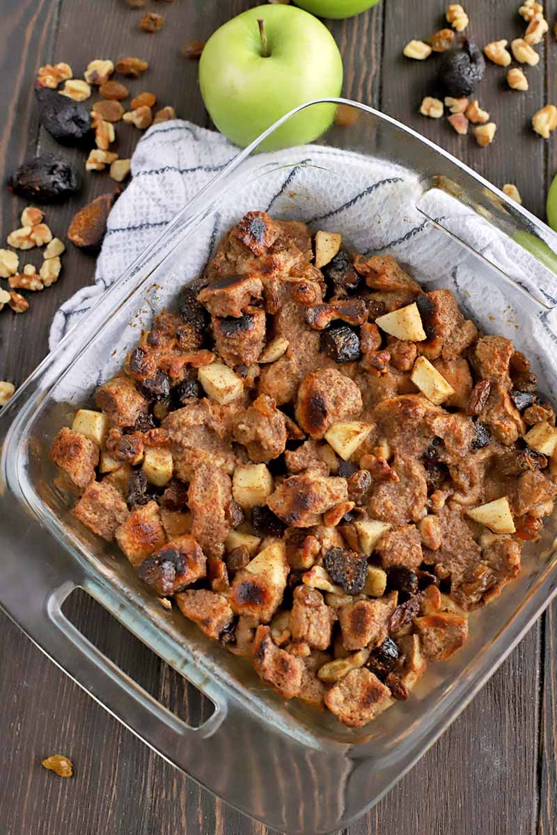 Overhead shot of a glass baking dish of homemade bread pudding with a light green apples, and scattered dried fruit and nuts, on a dark brown wood surface.