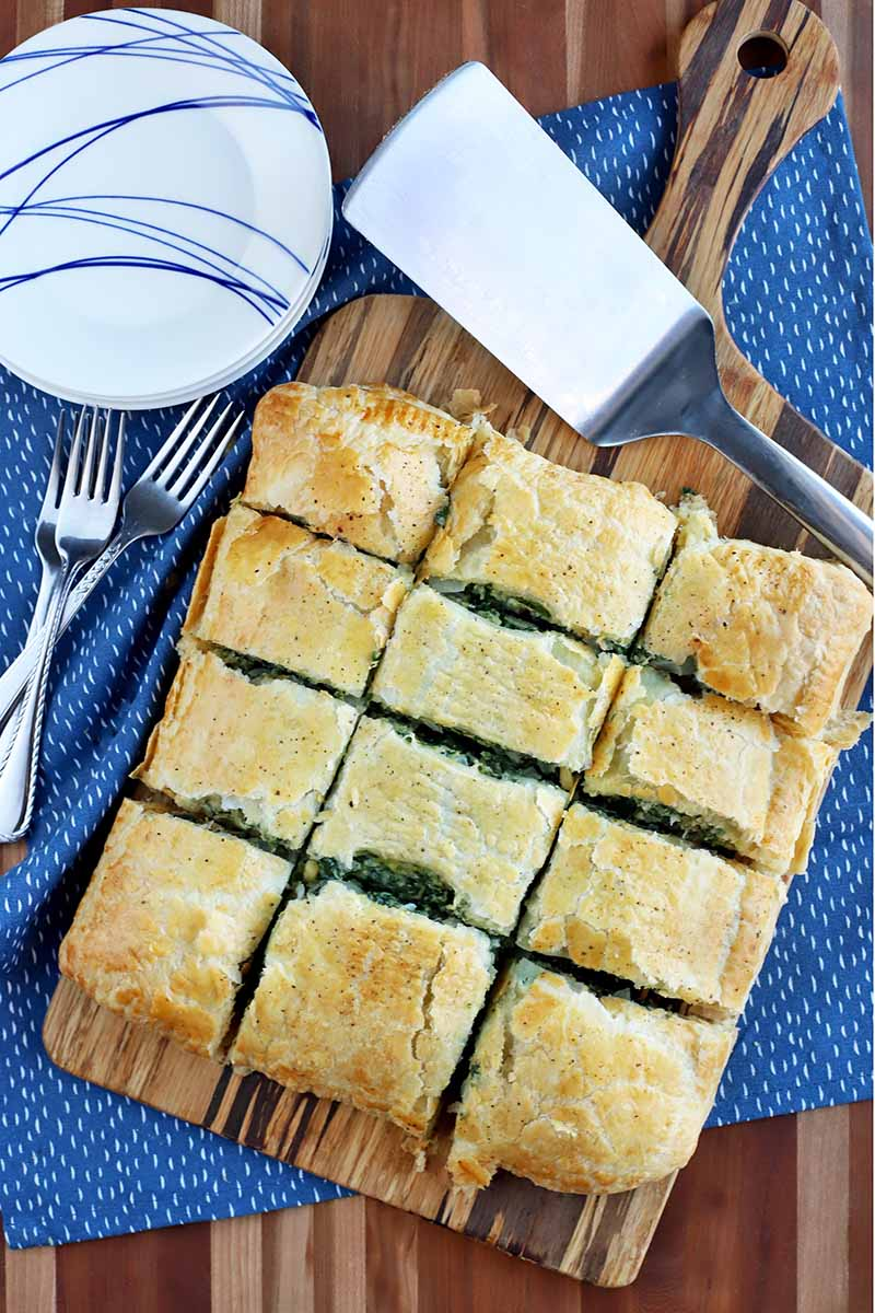 Overhead shot of homemade spinach in puff pastry cut into twelve slices and arranged on a wood board with a handle, with a metal spatula, a small stack of blue and white plates, and several forks, on a blue place mat on a striped wood table top.