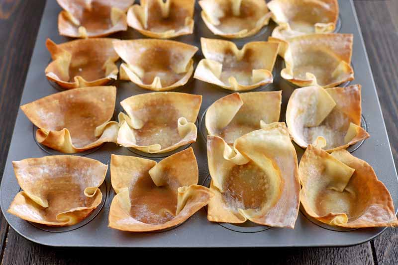 Baked wonton wrapper cups arranged in rows in a mini muffin tin, on a dark brown wood background.