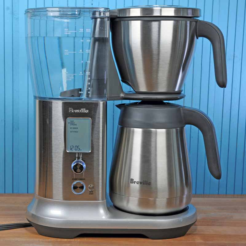 The Breville BDC450 Precision Brewers sitting on a maple butcher block table with a blue background.