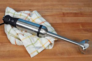 Top down of the All-Clad KZ750D Stainless Steel Immersion Blender sitting on a dish towel and maple wooden butcher board surface.