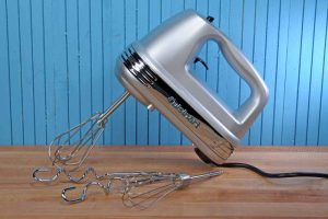 The Cuisinart HM-90BSC Power Advantage Plus 9 Speed Hand Mixer sitting on a maple wooden butcher block counter with a bead board background painted a medium blue.
