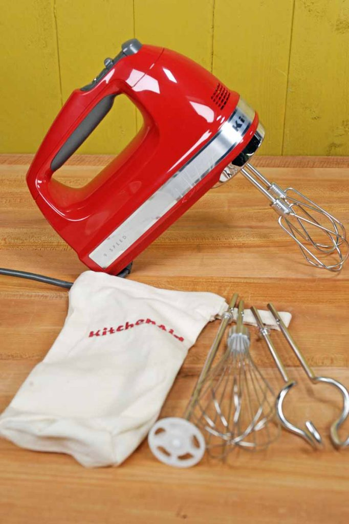 An Empire Red version of the KitchenAid KHM926ER 9-Speed Hand Mixer with attachments, cloth storage bag on maple butcher block table.