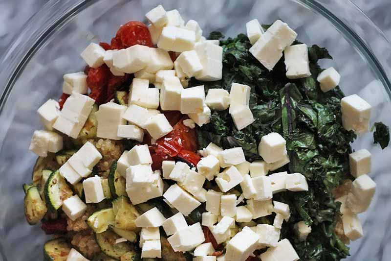 Closely cropped shot of a large glass mixing bowl filled with a mixture of quinoa and vegetables, topped with diced feta cheese, on a marble surface.