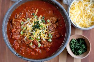 Overhead shot of a bowl of chili with smaller bowls of shredded cheese and chopped fresh cilantro, on a striped light brown wood surface.