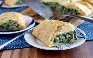 A plate of spinach in puff pastry in the foreground with more on two plates and a wood board in the background in soft focus, with a metal spatula and a blue and white place mat, on a brown wood surface.