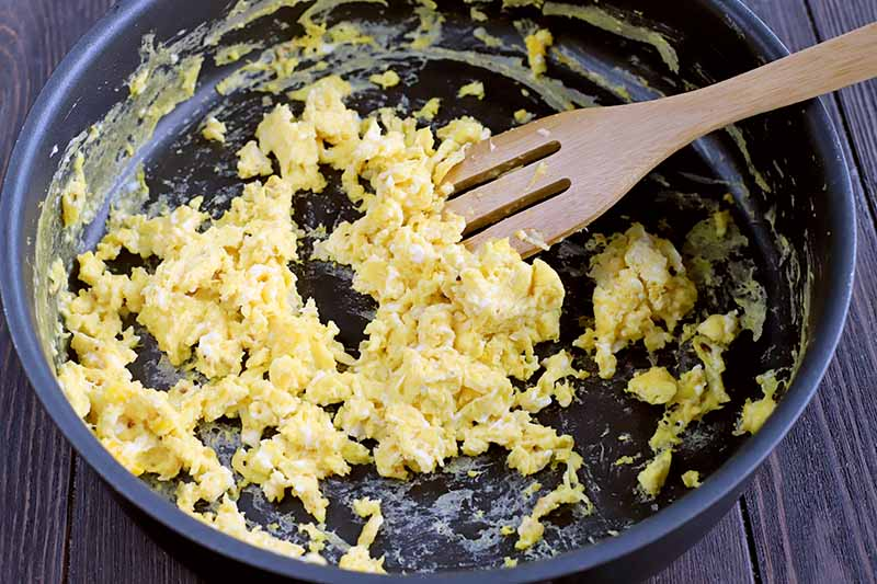 Closeup of eggs being scrambled in a large nonstick frying pan and stirred with a slotted wooden utensil, on a dark brown wood surface.