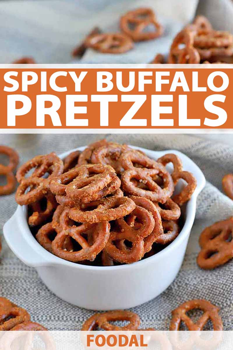 Vertical image of a white ceramic dish of spicy buffalo pretzels, with more scattered around it on a folded and gathered beige cloth, printed with white and orange text.
