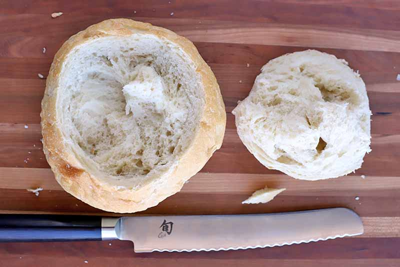 Overhead shot of a boule loaf with the top removed and placed next to it, with a serrated knife at the bottom of the frame, on a striped light and darker brown wood surface.