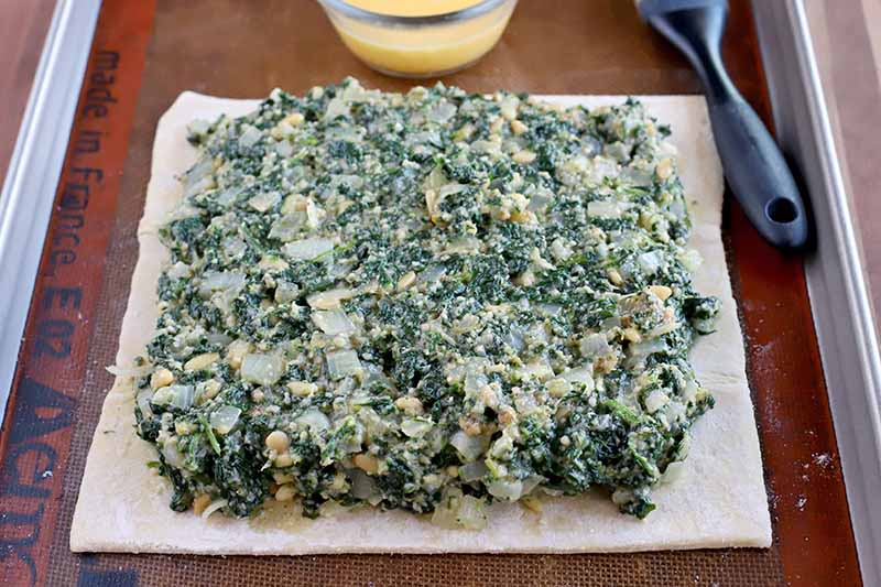 A spinach and onion mixture spread over the surface of a square piece of puff pastry with a slight border left around the perimeter, on a silicone pan liner set into a rimmed metal baking sheet, with a small glass bowl of egg wash and a black-handled silicone brush.