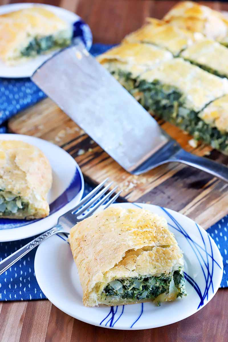 Vertical oblique shot of three plates and a board topped with square portions of spinach in puff pastry, with a metal spatula, on a blue cloth on top of a wood surface.
