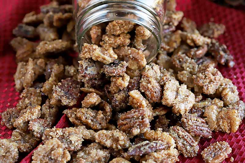 Sugar and spice candied nuts spilling out of a glass mason jar.