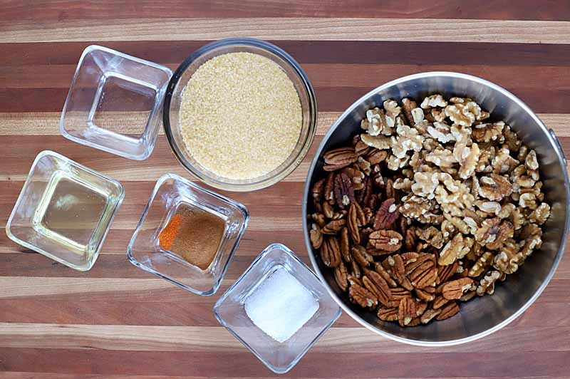 Top-down view of the ingredients in measuring cups and mixing bowls needed to make sugar and spice candied nuts.