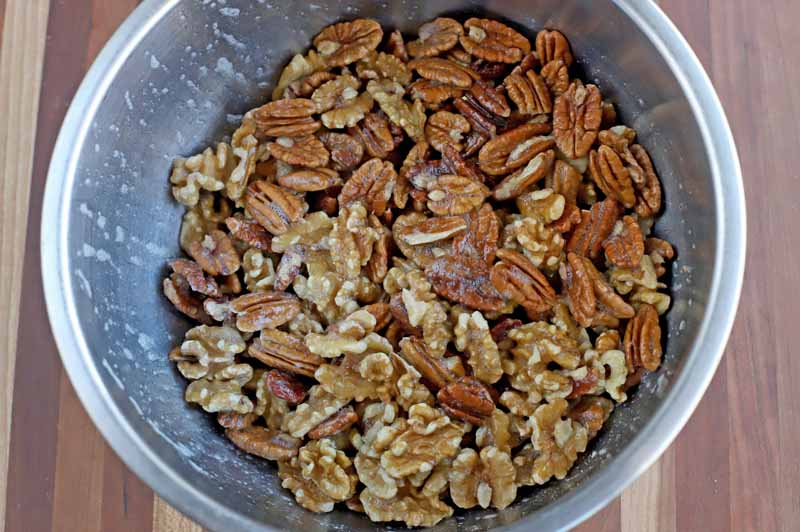 Nut mixture with wet mix added to a stainless steel mixing bowl.
