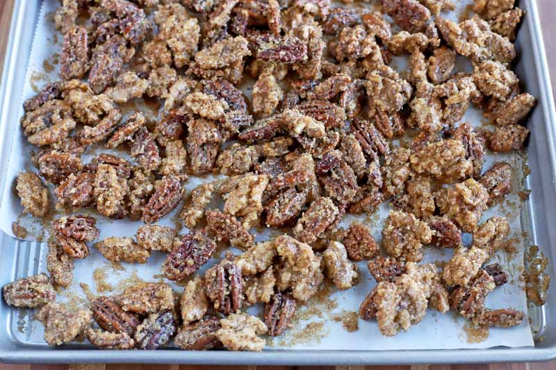 Sugar and spice candied walnuts and pecans laid out on a baking sheet.