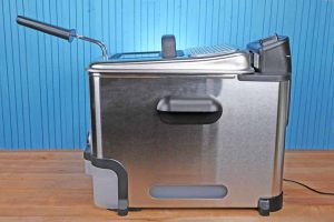 The T-fal Ultimate EZ Clean Fryer sitting on a butcher board table with a medium blue background.