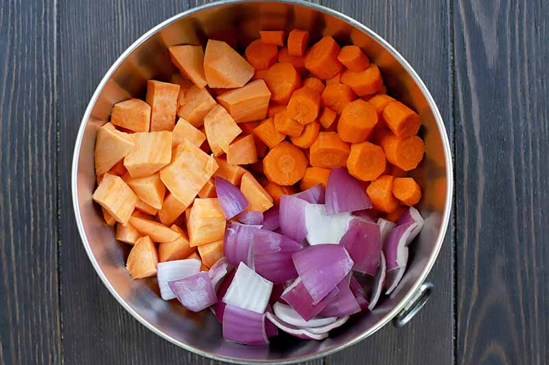 Overhead shot of a stainless steel mixing bowl with a ring handle, filled with peeled and chopped carrot, sweet potato, and purple onion, on a dark brown wood table.
