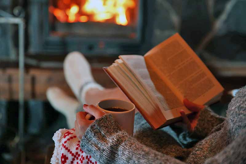 Closely cropped image of a person in a gray sweater holding a mug of coffee with their left hand and a book with their right, sitting in a recliner chair with their feet up in front of a fireplace, shot from behind.