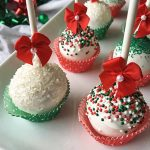 Horizontal image of assorted white dessert pops in cupcake liners decorated with sprinkles and bows.
