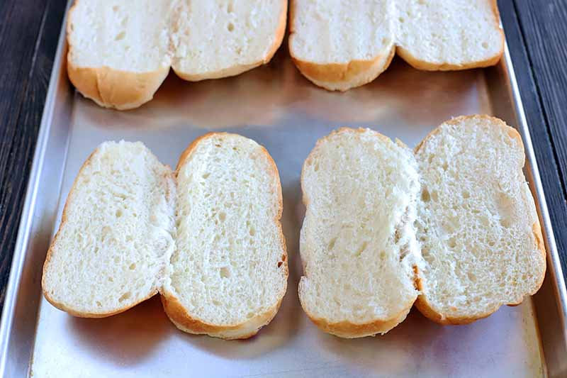 Four sandwich rolls have been cut in half and arranged on a rimmed metal baking sheet, on a dark brown wood surface.