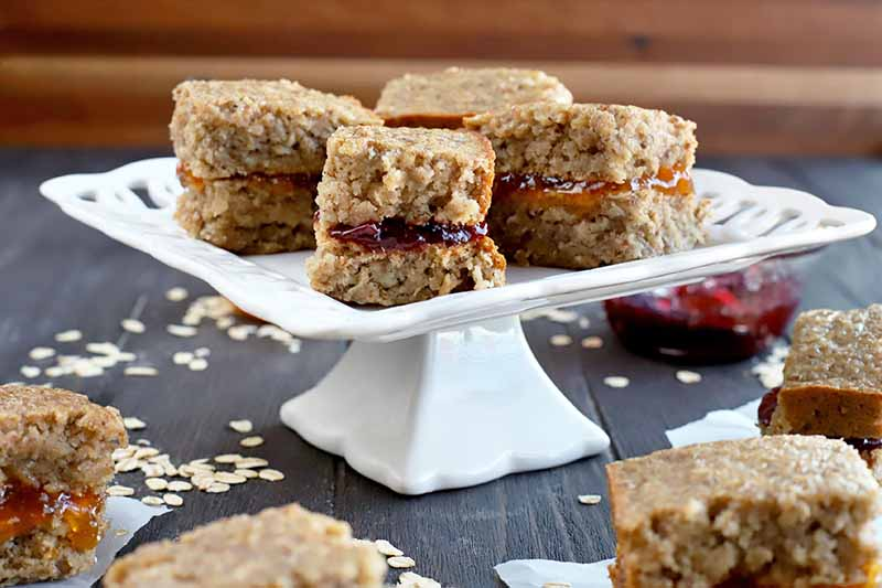 A square ceramic pedestal-style serving platter topped with four gluten-free homemade sandwich bars filled with fruit jam, on a dark brown wood table surrounded by more bars on square pieces of parchment paper and scattered uncooked oats, against a brown striped backdrop.