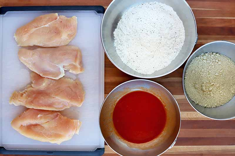 Overhead shot of four raw chicken breasts on a black and white plastic cutting board, with three bowls of flour, hot sauce, and breadcrumbs, on a striped wood surface.