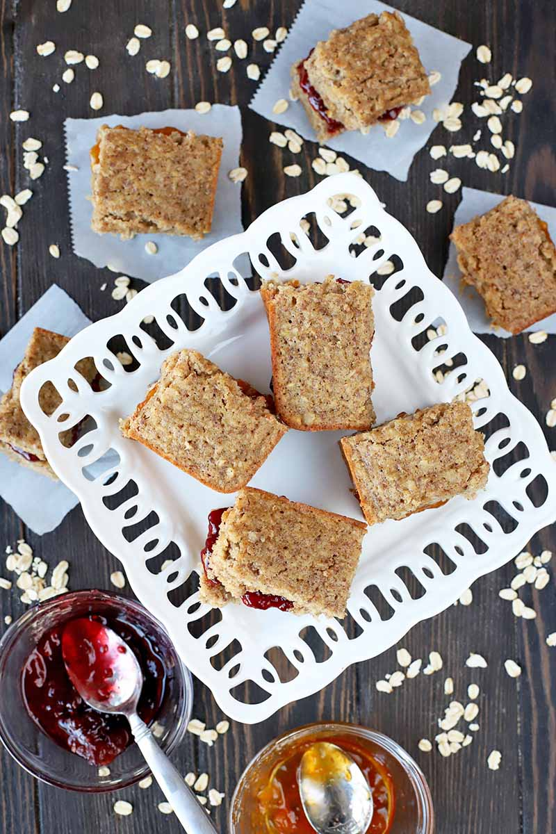 Overhead vertical shot of gluten-free breakfast bars on a square decorative serving dish and squares of parchment paper, with two small glass bowls of red and orange fruit jam with spoons stuck into them, surrounded by scattered uncooked oats on a dark brown wood table.