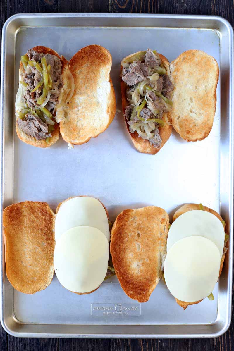 Overhead vertical shot of three mini hoagie rolls that have been sliced in half and toasted, then topped with sliced steak and provolone cheese, on a rimmed metal baking sheet.