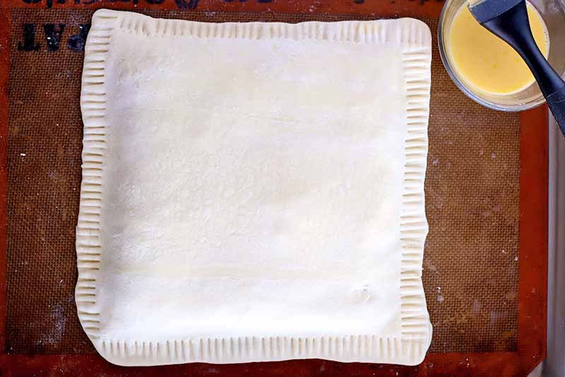 Overhead shot of a square of filled puff pastry with fluted edges on a beige and orange Silpat silicone pan lines, with a small cup of egg wash and a silicone brush.