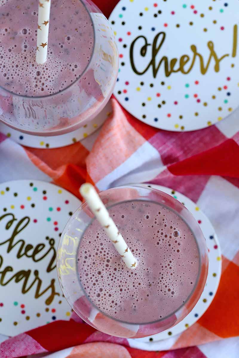 """Overhead vertical shot of two glasses containing a pink fruit smoothie, with white paper straws printed with metallic gold stars, on a red and white checkered cloth with decorative paper coaster printed with """"Cheers"""" in gold."""