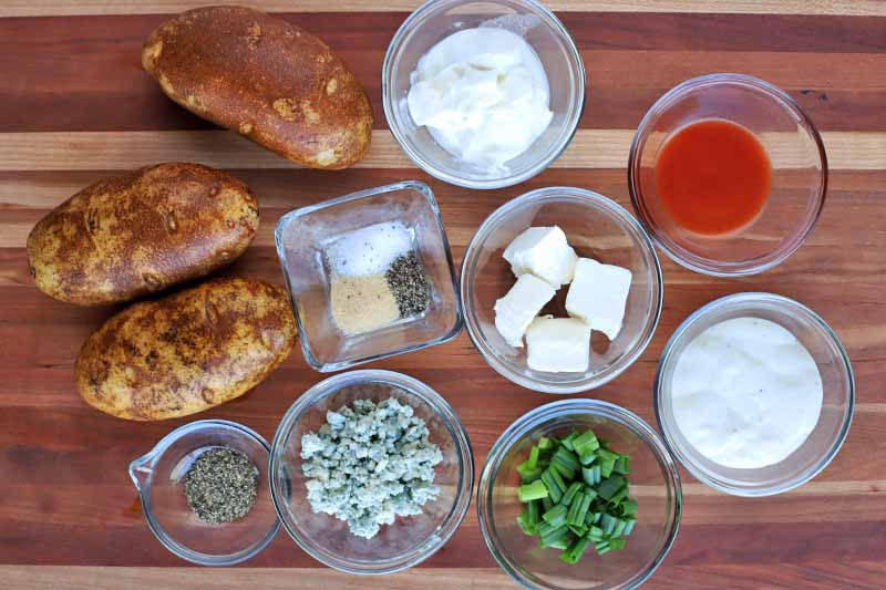 Horizontal image of potatoes and assorted ingredients in small bowls on a cutting board.