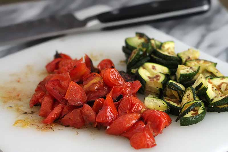 Chopped roasted tomatoes and zucchini on a white plastic cutting board, with a chef's knife in soft focus in the background on a marble surface.