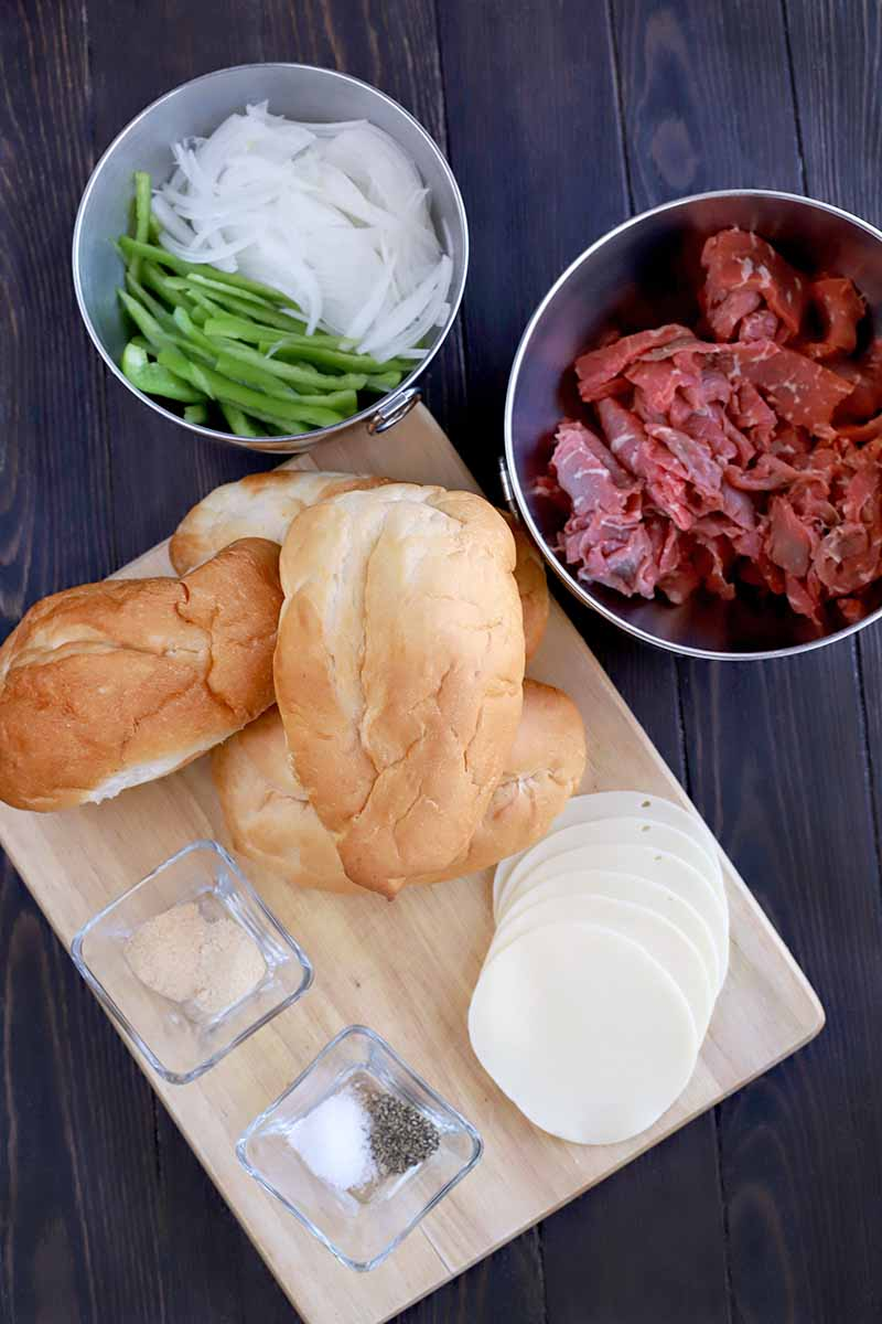 Overhead vertical shot of a small stainless steel bowl of sliced green bell pepper and onion beside another filled with thinly sliced beef, next to a wood cutting board topped with mini hoagie rolls, sliced provolone cheese, and two small glass dishes of salt, black pepper, and other spices, on a dark brown wood surface.
