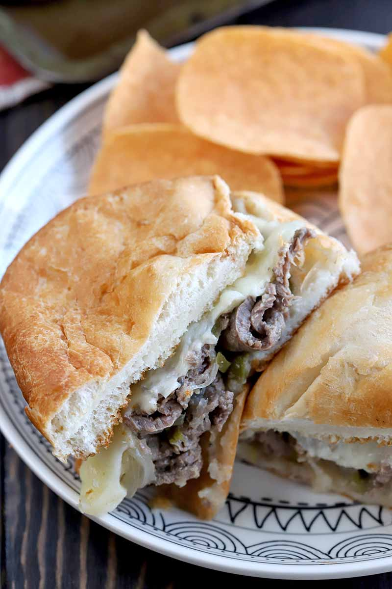 A homemade cheesesteak sandwich has been sliced in half to show the filling inside, and arranged on a white plate with a black decorative pattern alongside a pile of cheese-flavored Pringles, on a dark brown wood surface.